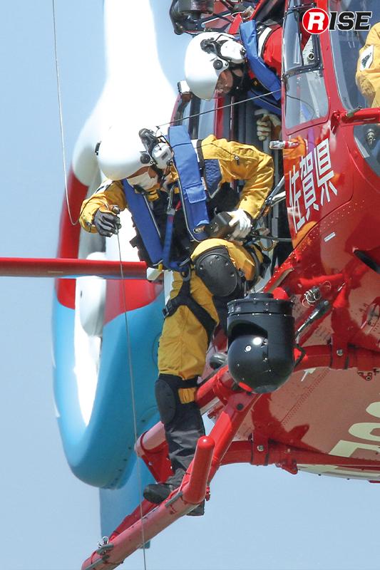 ホイストケーブルを巧みにさばき、降下隊員をサポート。あわせて、死角が広くなる機体直下での活動のため隊員らが周囲の監視を行う。
