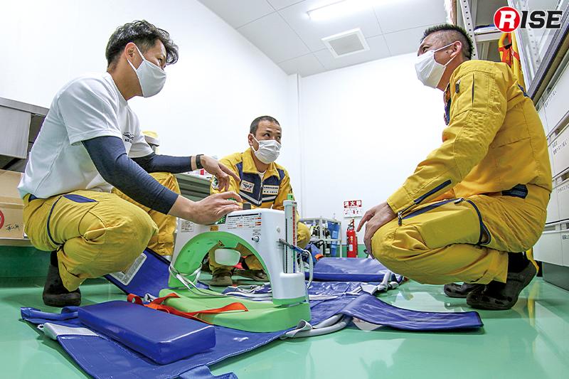 自動心臓マッサージ機の点検を行う救命士3名。