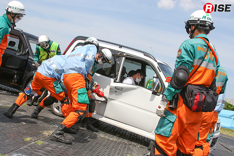 【多重衝突事故現場における道路啓開・救出救助訓練】油圧救助器具によりドア開放を図る機動救助隊の隊員たち。
