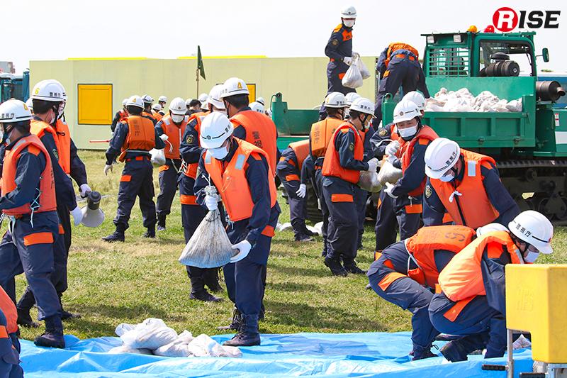 【避難誘導・水防工法訓練】大量投入された土のうを機動隊員らが迅速に設定箇所へ移動させ積み上げる。
