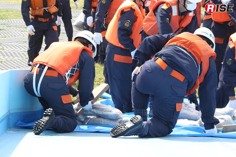 【避難誘導・水防工法訓練】隙間がなくなるよう土羽打ち道具で叩きながら積み上げていく。